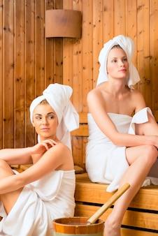 Amies dans un spa de bien-être profitant d'infusion de sauna