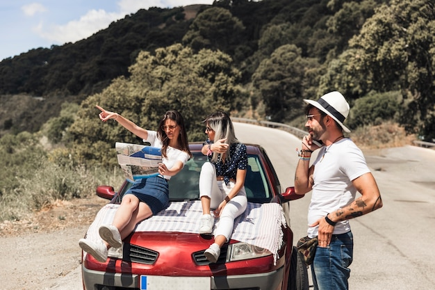 Amies discutant de la direction sur la carte en face de l'homme parlant au téléphone mobile