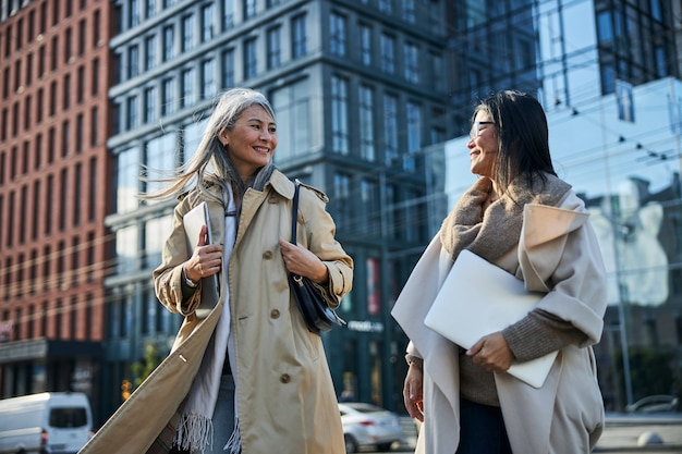 Amies élégantes avec des ordinateurs portables debout dans la rue