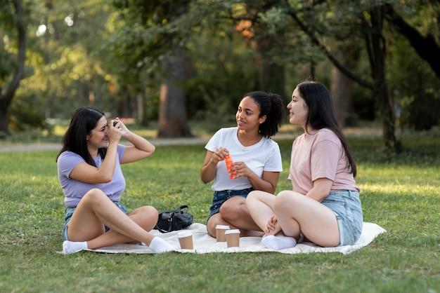 Amies ensemble au parc à prendre des photos