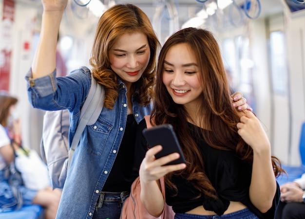 Des amies ethniques ravies montant un train moderne et regardant ensemble une vidéo sur un téléphone portable