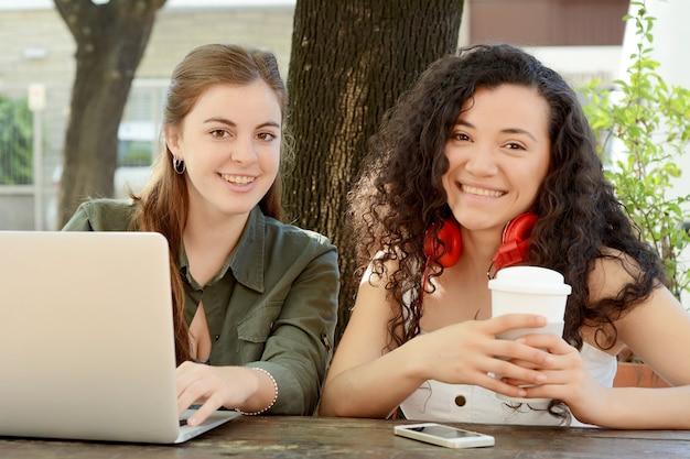 Amies étudient avec un ordinateur portable dans un café.