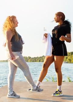 Amies faisant le salut de la cheville tout en faisant de l'exercice au bord du lac