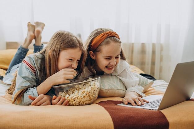 Amies de filles regardant un film en ligne et mangeant du pop-corn