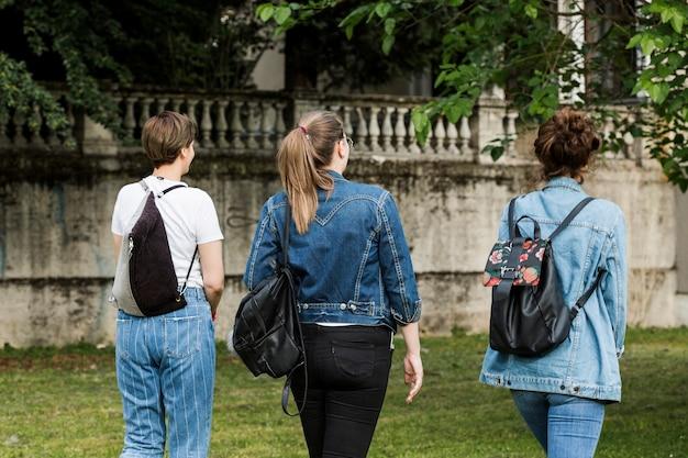 Amies marchant sur la pelouse du parc