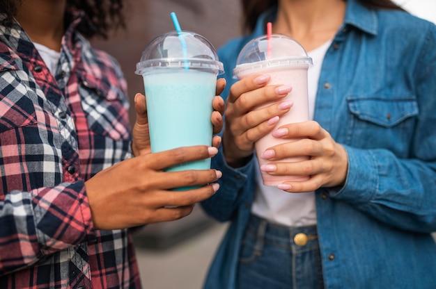Amies avec milkshakes à l'extérieur ensemble