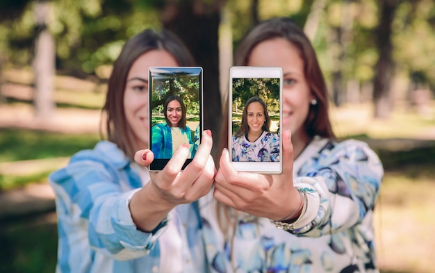 Des amies montrant des smartphones avec leurs photos de selfie ont envahi une forêt