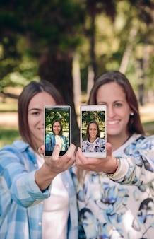Amies montrant des smartphones avec leurs photos de selfie prises sur fond de forêt