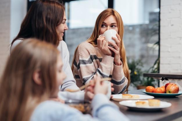 Amies et une petite fille assises ensemble à la table de la cuisine, buvant du café et parlant