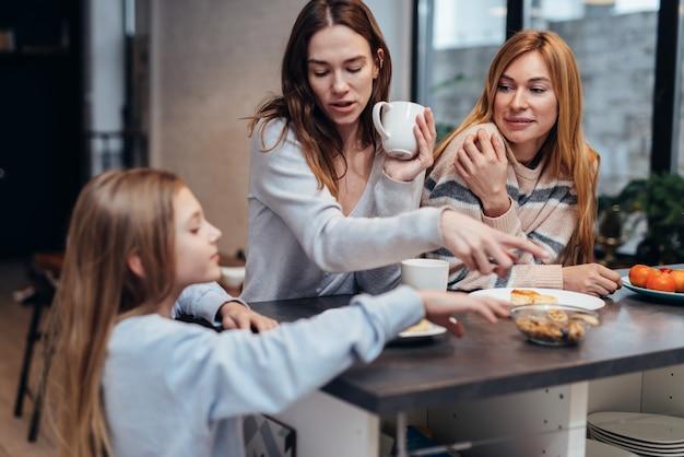 Des amies et une petite fille assises ensemble à la table de la cuisine, buvant du thé et parlant.