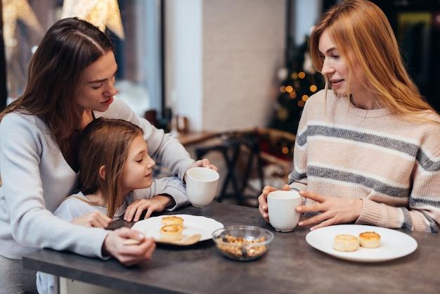 Des amies et une petite fille assises ensemble à la table de la cuisine.