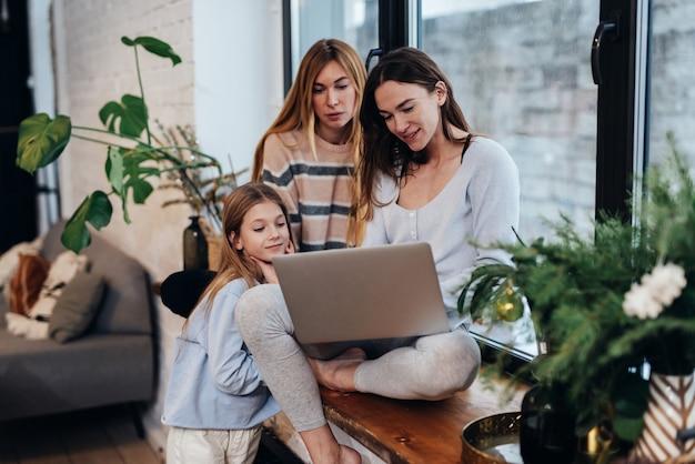 Des amies et une petite fille s'assoient ensemble et regardent l'écran de l'ordinateur portable.