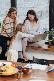 Des amies et une petite fille sont assises à la maison sur un rebord de fenêtre et regardent une série.