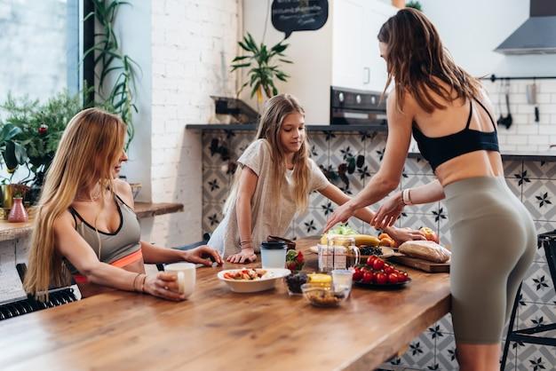 Des amies et une petite sœur préparent un repas léger de légumes, de fruits et de salade pour une collation après l'entraînement.