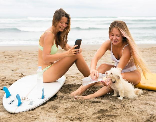Amies à la plage avec chien et smartphone