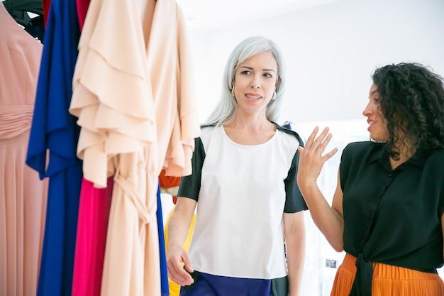 Amies positives faisant du shopping ensemble. vendeuse aidant le client à choisir le tissu. coup moyen. magasin de mode ou concept de vente au détail