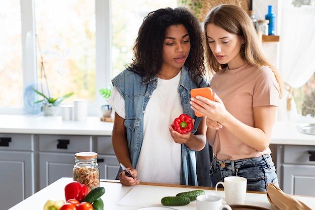 Amies à la recherche de recette sur smartphone pendant la cuisson