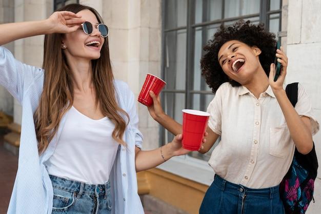 Amies s'amusant ensemble à l'extérieur avec des gobelets en plastique