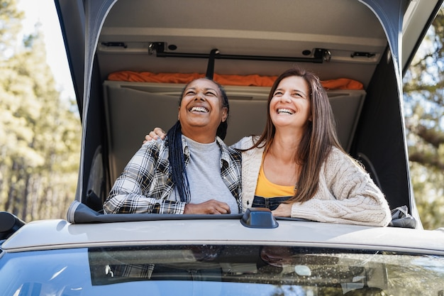 Amies seniors s'amusant à voyager dans les montagnes avec un camping-car - évasion dans la nature, concept multiracial et vacances