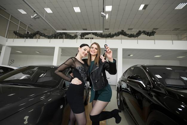 Des amies sont heureuses d'acheter une voiture chez un concessionnaire automobile