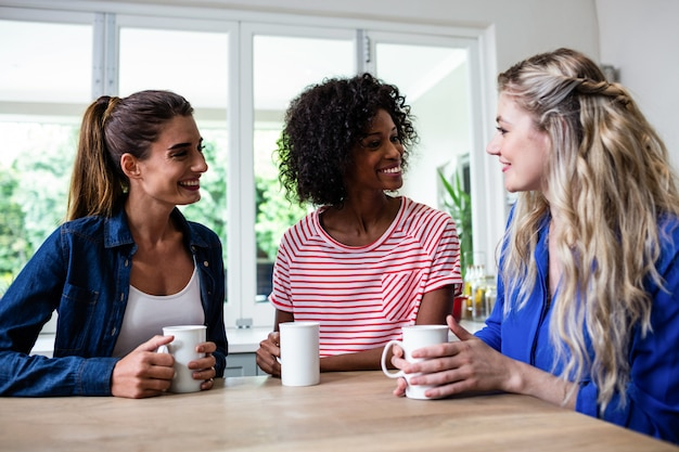 Amies avec une tasse de café assis à table