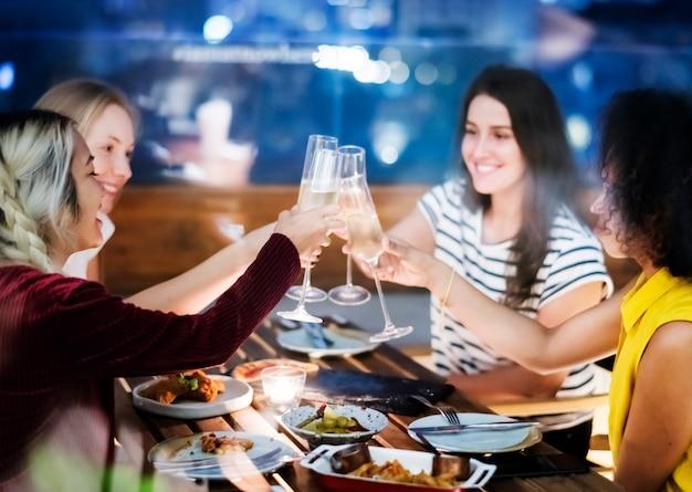 Des amies en train de griller au dîner ensemble dans un bar sur le toit