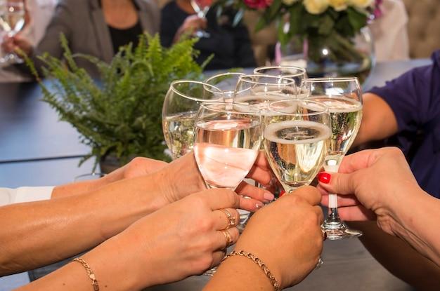 Des amies trinquent avec des verres à vin blanc.