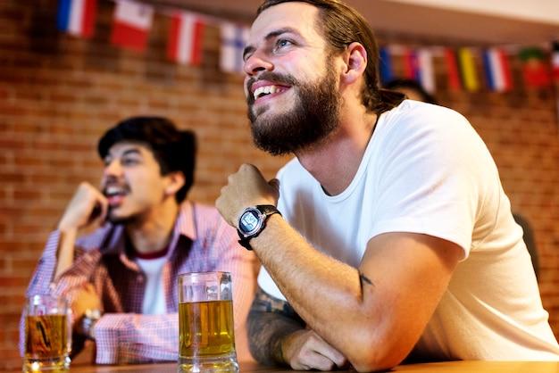 Amis acclamant le sport au bar ensemble