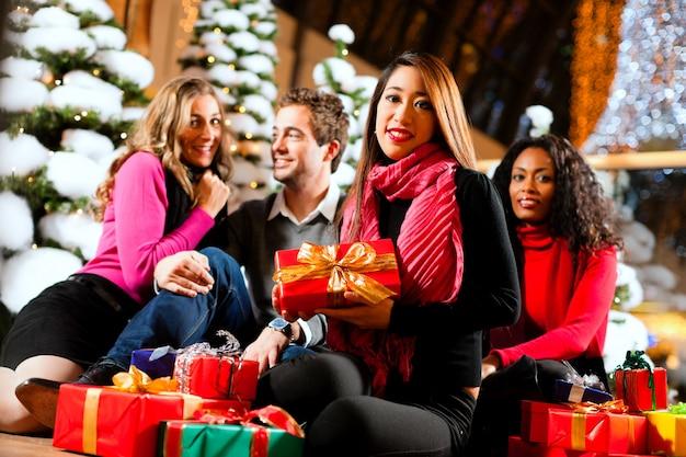 Amis, achats de noël avec des cadeaux au centre commercial