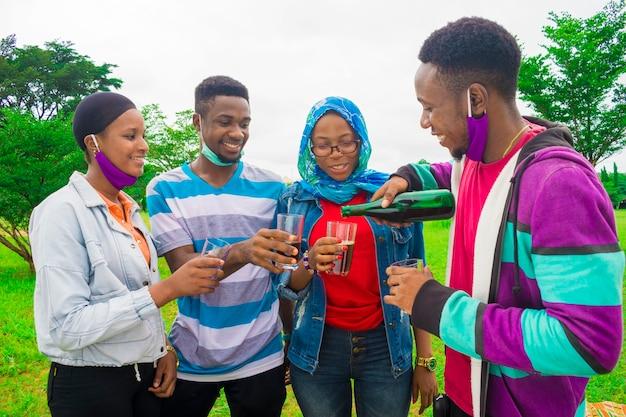 Amis africains heureux transformant la boisson en leur tasse - concept d'amitié