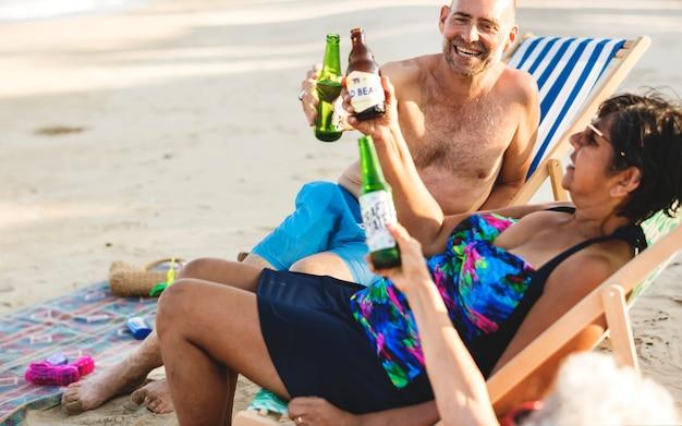 Amis d'âge mûr ayant des bières à la plage