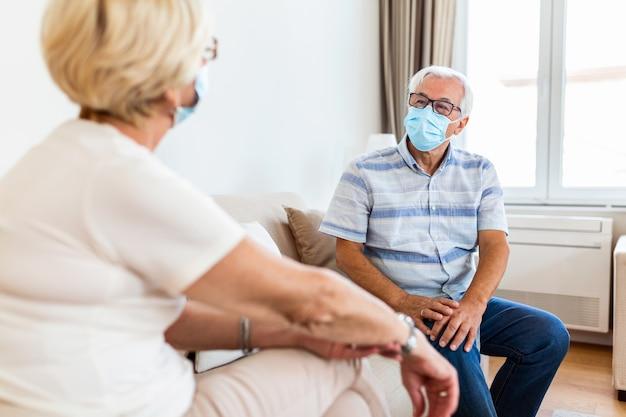 Des amis aînés ayant une conversation sur le canapé à la maison pendant la pandémie de covid 19