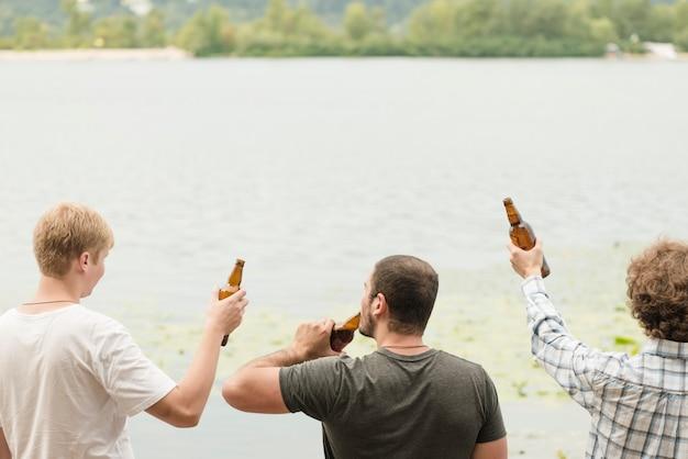 Amis anonymes profitant de la bière près de l'eau