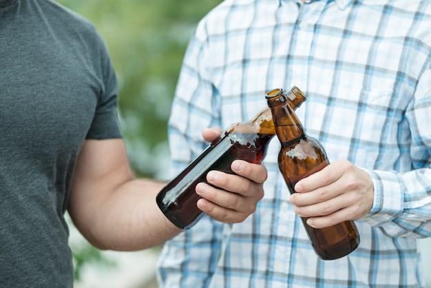 Amis anonymes en train de tinter des bouteilles de bière