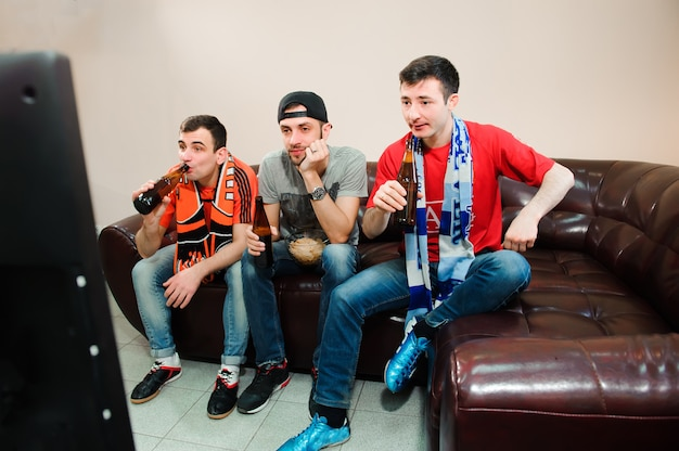 Amis applaudir et boire de l'alcool tout en regardant un match de football à la télévision.