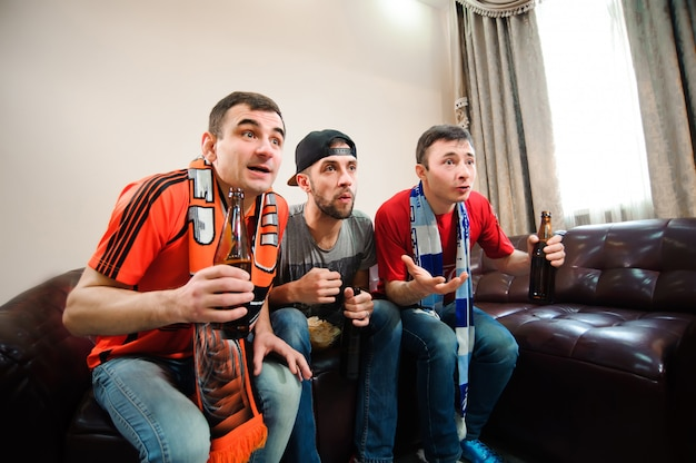 Amis applaudissant et buvant de l'alcool tout en regardant un match de football