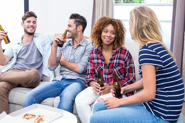 Amis appréciant une bière assis sur un canapé à la maison