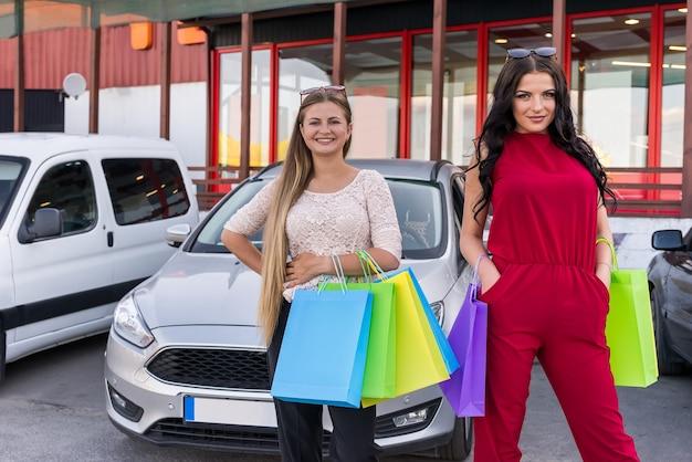 Amis après avoir fait du shopping avec des sacs colorés sur le parking
