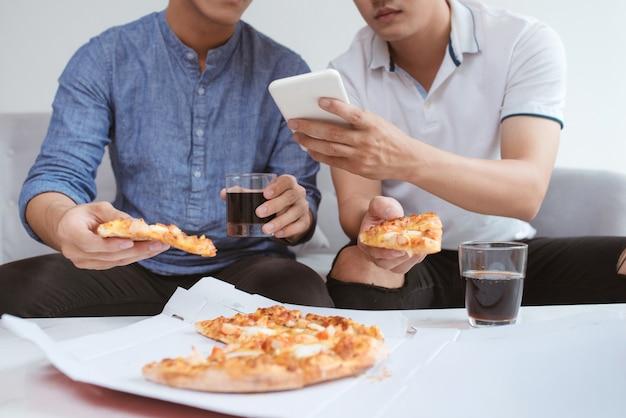 Amis asiatiques appréciant sa pizza assis sur un canapé devant la télévision à la maison.