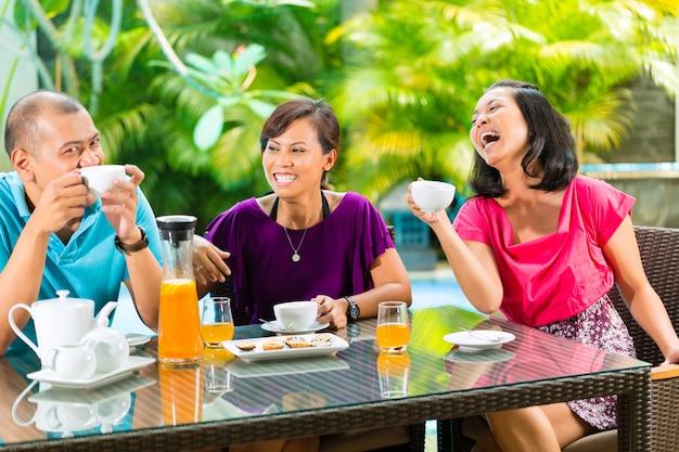 Amis asiatiques ayant un café sur le porche de la maison