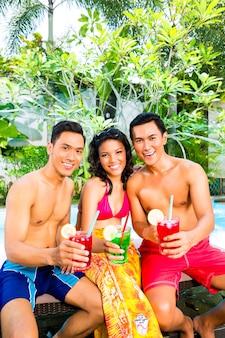 Amis asiatiques buvant des cocktails au bord de la piscine