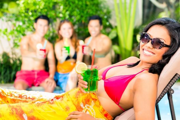Amis asiatiques faire la fête à la fête de la piscine dans la station