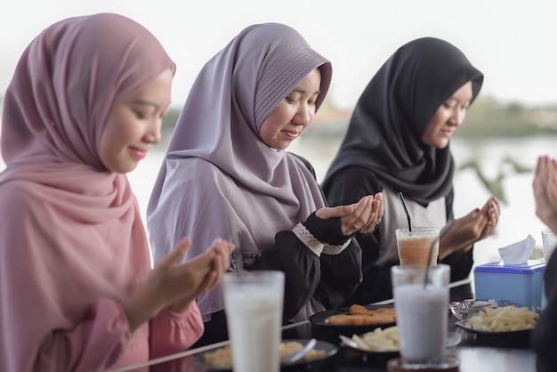 Des amis asiatiques musulmans prient ensemble quand ils jeûnent dans un café