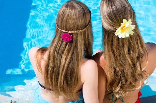 Amis assis au bord de la piscine