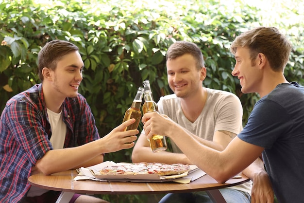 Amis assis dans un café avec de la bière fraîche et de savoureuses pizzas