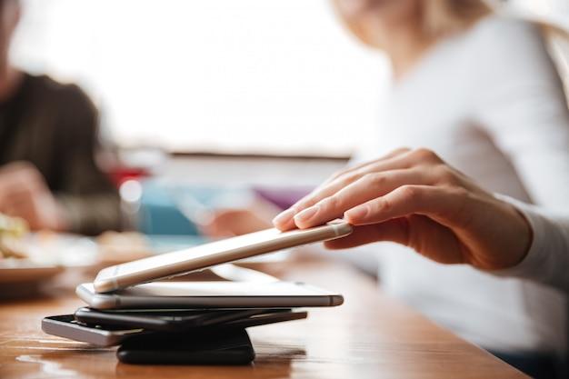 Amis assis dans un café. femme touchant le téléphone.