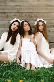 Amis assis dans l'herbe avec des fleurs tiare