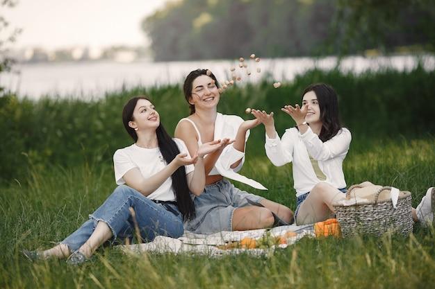 Amis assis sur l'herbe. les filles sur une couverture. femme en chemise blanche.