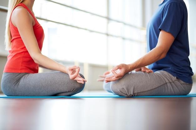 Amis assis les jambes croisées pendant la méditation