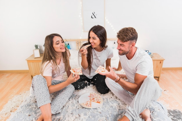 Amis, assis sur un lit avec des plumes à tartiner mangeant des pizzas
